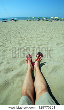 Adult With Long Legs And Flip Flops At The Foot Rests On The Sand Of The Beach