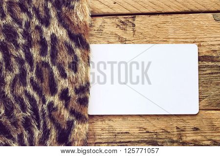 faux fur leopard and empty paper tag lying on a wooden table