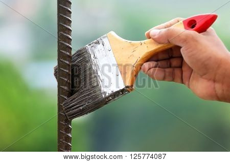 Painting an iron rod outdoor with a brush