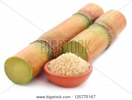 Piece of sugarcane with sugar in a brown pottery