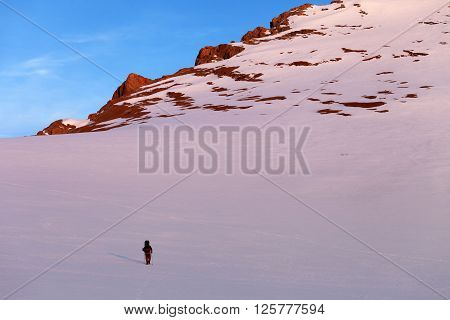 Hiker In Sunrise Snowy Mountains