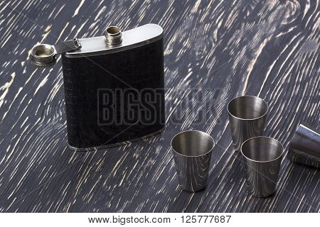 Metal flask trimmed leather and four metallic, sturdy shot glasses on a wooden background