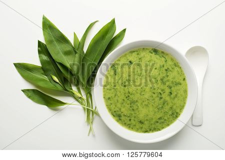 Fresh wild garlic soup on white background overhead shoot