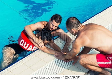 Lifeguards with victim on poolside with drowner