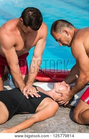 Lifeguards in CPR training, vertical image, close up