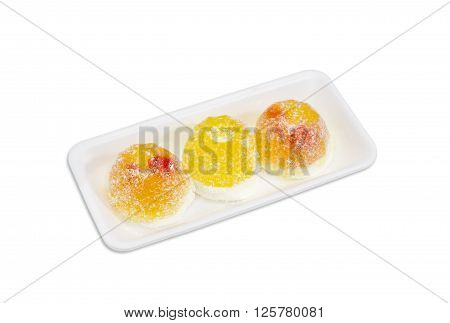 Three yellow fruit jelly candies gelatin based with jam inside and coated in granulated sugar in a small plastic tray on a light background