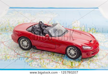 Children's red toy car cabriolet on the open road atlas
