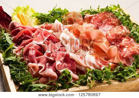 Salami Cold Cuts In Box Surrounded With Greens