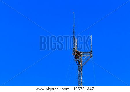 Tall, large, cell phone tower against a blue  sky