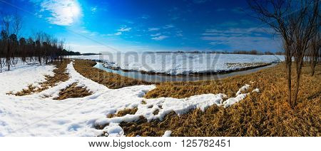 Spring landscape with a brook behind a snow mound . Siberia, Yugra.