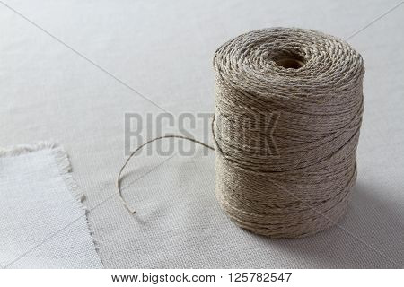 Big bobbin with thread lying on the table. Texture background
