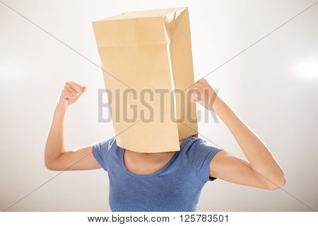 Woman cover a paper bag with her head and showing biceps