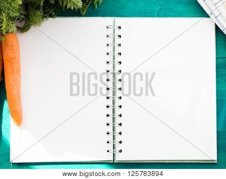 Open paper note book with blank pages on dark green table with paddock carrots and a napkin at the sides