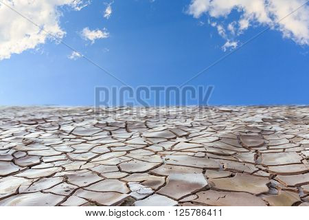 Cracked land with blue sky and clouds
