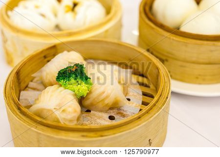 Three transparent shrimp dumplings with transparent skin in a steamer