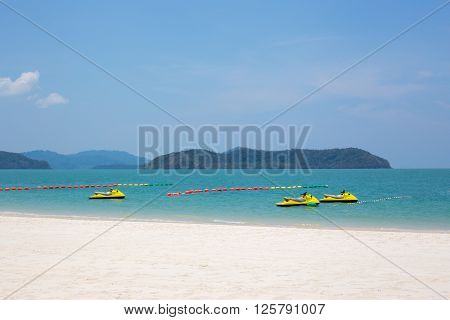 Three yellow watercrafts in the water on Langkawi island Malaysia