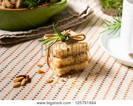 Home made butter cookies with rosemary, pignoli and pistachio nuts on table cloth with rosemary sprigs and a hot beverage in the background