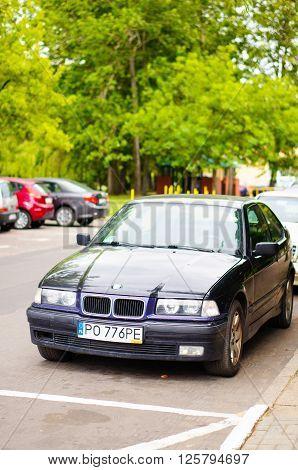 POZNAN POLAND - JUNE 19 2014: Parked BMW car by a sidewalk on the Piastowskie area