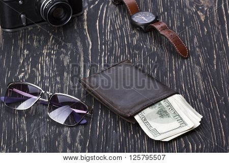 gentlemanly set:  sunglasses, wallet with money, camera and watch on wooden background