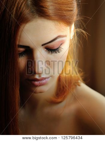 Beautiful young red-haired woman portrait looking down