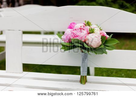 Wedding bouquet. Bride's traditional symbolic accessory. Floral composition with pink peony flowers on garden bench.