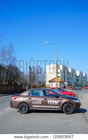 POZNAN POLAND - MARCH 17 2016: Parked AMC company car by a sidewalk on the Stare Zegrze area