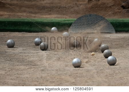 Petanque ball boules bawls on a dust floor,photo in impact