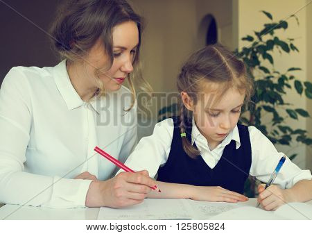 Mother Helping Daughter With Homework At Home. Vintage Effect.