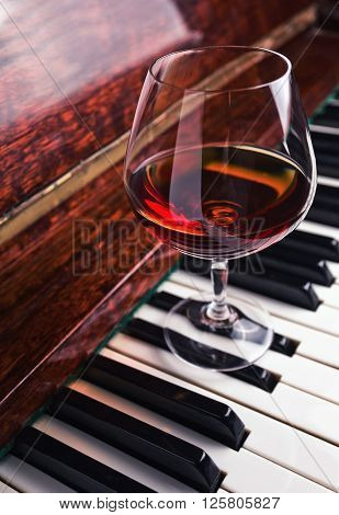 snifter of brandy on a old piano