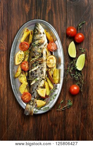 Grilled fish with potato wedges on wooden background top view