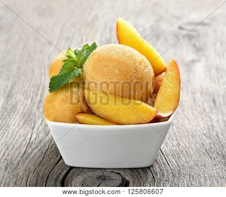 Peach sorbet ice cream with slices in bowl on wooden background