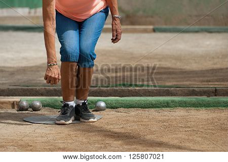 Senior playing petanque, balls on the ground