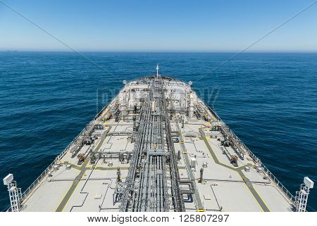 Grey crude tanker ship proceeding to skyline of the deep blue sea