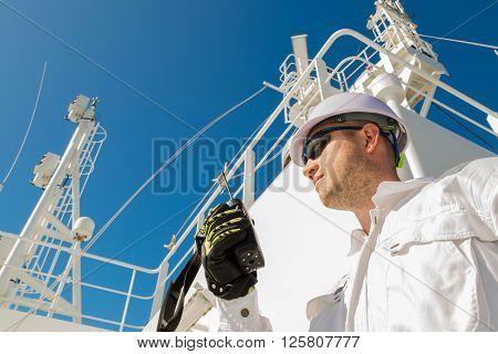Deck officer speaking by VHF on radar deck under blue sky