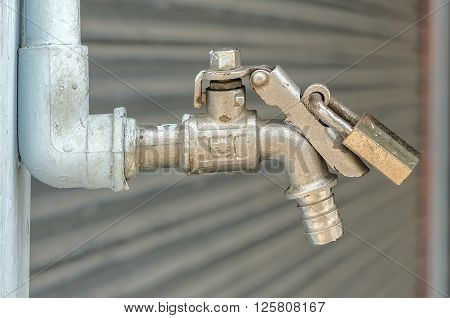 Old faucet with padlock prevents water theft. Concept of save water.