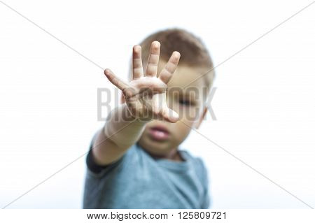 Portrait of little handsome boy showing stop with his hand isolated on white background.