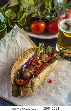 Tasty hotdog with grilled sausage tomato onion and lettuce on the background of beer glass and vegetables. Fast food. Selective focus.