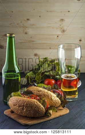 Two delicious hotdogs with sausage and vegetables beer bottle and glass on wooden table. Fast food and alcoholic drink.