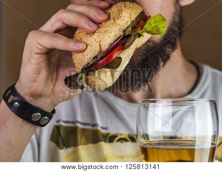 Bearded man eating hotdog and drinking beer. Fast food and alcohol.