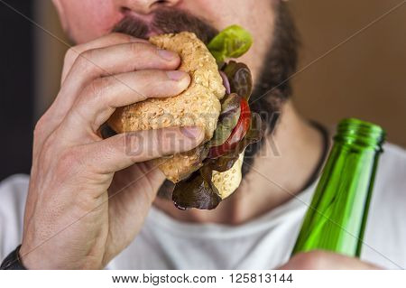 Bearded man eating hotdog and holding beer bottle. Fast food and alcohol.