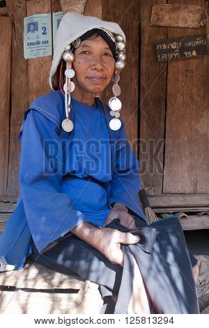 MAE SALONG,  CHIANG RAI province , THAILAND - JUN, 2004 :  In the mountains of northern Thailand. An old woman from the Akha ethnic group. To save her money Akha women sew silver coins on headdress.