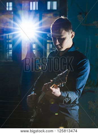 Portrait of yong guitarist playing on electric guitar