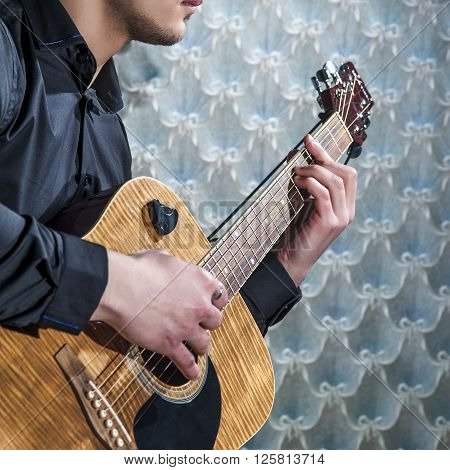 Young Man playing on acoustic guitar,  closeup.