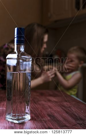 Home violence: Drunk woman and her little child in kitchen. Alcoholic addiction. Focus on bottle.
