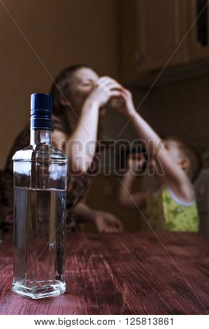 Child asks mother stop drinking. Family problems alcoholic addiction. Focus on bottle.