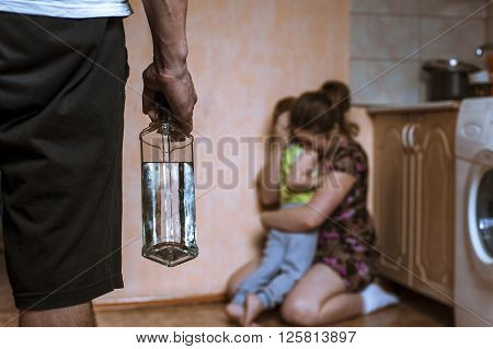 Woman covering her child from angry drunk father. Domestic violence.