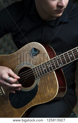 Young guitarist playing on acoustic guitar. Vertical view