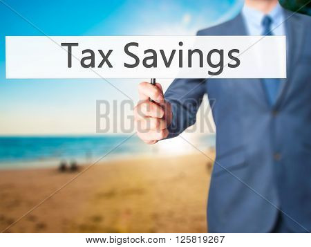 Tax Savings - Businessman Hand Holding Sign