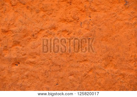 Orange painted old dirty concrete plaster wall with paint racks defects and stains