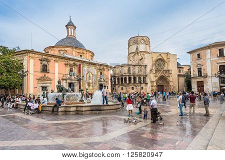 Valencia Spain - May 18 2014: Fountain at the Plaza de la Virgen with Basilica in the background. People are scattered over the square in cloudy weather.